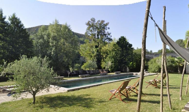 Gîtes de France - Au Château d'Uzer, près de la rivière, la piscine façon grand bassin de nage ourlé de pierre (18mx4,5m), ses plages et ses estrades.